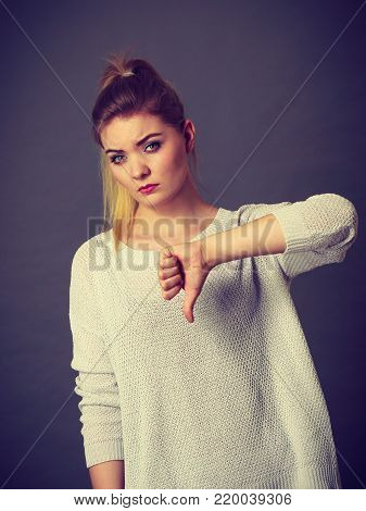 Sad unhappy woman showing thumb down gesture. Negative human face expressions and gestures concept.