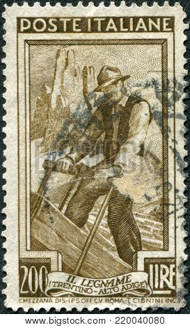 ITALY - CIRCA 1950: A stamp printed in Italy, shows the Woodcutter, the background Vajolet Towers (South Tyrol), circa 1950