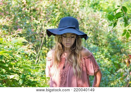 Caucasian teenage girl in sunlit summer woods with serious expression wearing black hat and off the shoulder blouse