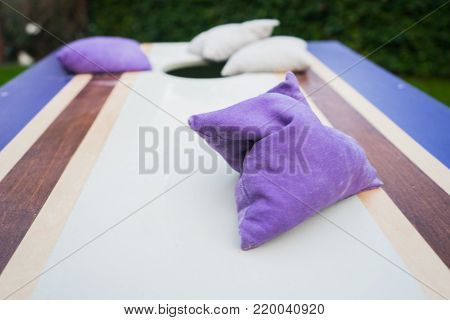 Purple Wooden Cornhole Game Board With Beanbags On Grass