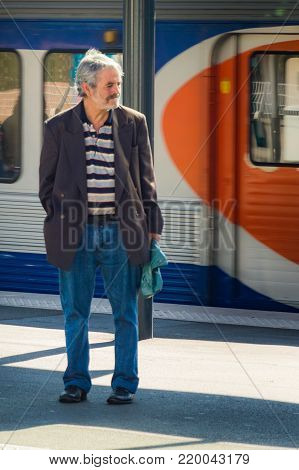 Old men in Paris on platform on railway station. Local French commuter going to work or vacation. Tourist using subway or intercity train in France. Parisian old men in a subway station. France, Paris, September, 27, 2014