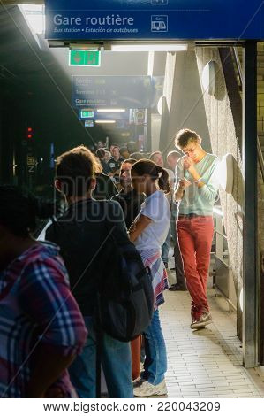 Young man in Paris on platform on railway station in sun ray. Local French commuter going to work or vacation. Tourist using subway or intercity train in France. Parisian guy in a subway station. France, Paris, September, 27, 2014