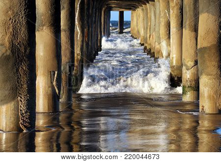 Under Manhattan Beach Pier, Los Angeles, California. Perspective with waves and pilings looks like a corridor.