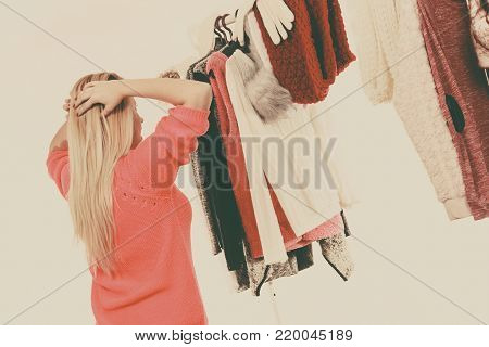 Young woman standing in wardrobe or in mall shop, choosing warm clothes, deciding what to wear or buying. Picking winter autumn clothing concept. Back view, filtered image