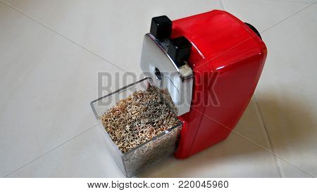 Red Pencil Sharpener with Shavings in Transparent Container