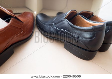Close up black leather shoes on brown background