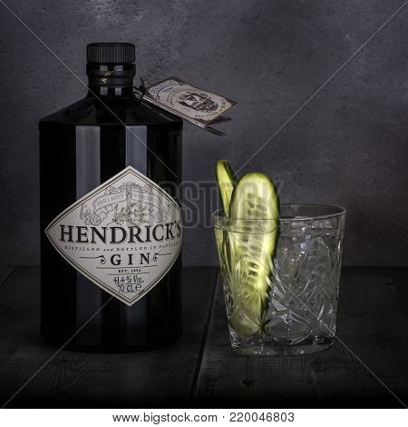 SWINDON, UK - DECEMBER 27, 2017: 70 cl bottle of Hendricks distilled gin with a glass and Cucumber on a Dark Rustic background