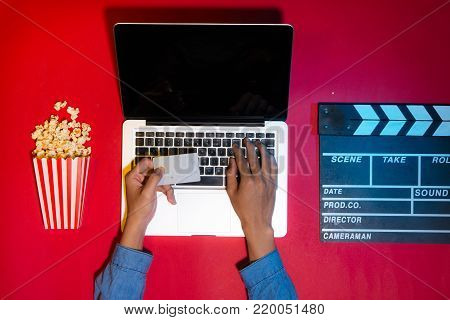Man holding a credit card paying ticket online with popcorn and clapboard. Movies and cinema concept