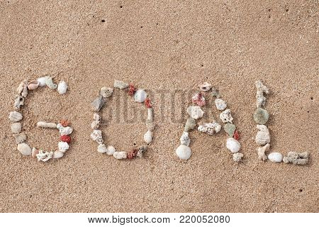 Goal word made from shells on sandy beach. Concept of achievement in business