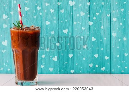 Homemade iced chocolate or cacao in glass. Iced chocolate or cacao on white wood table and blue background with snowfall and cute heart shape. Concept to present bitter sweet and delicious drink on Valentine's day. Iced chocolate or cacao ready to served.