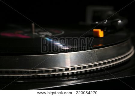 closeup of vinyl turntable, hi-fi headshell cartridge in action, Retro gramophone playing analog disc with music. place for text