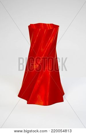 Abstract object of red color printed by 3d printer isolated on white background. Fused deposition modeling, FDM. Progressive modern additive technology. Concept of 4.0 industrial revolution