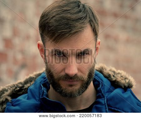 Portrait of a bearded man in winter clothes who looks aggressively. Serious businessman. Bearded Man.