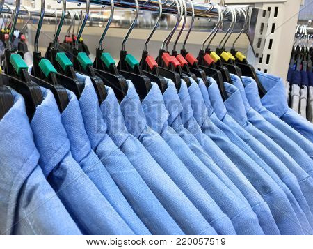 Same Styled Blue Shirts Hanging Hanging on a Rack