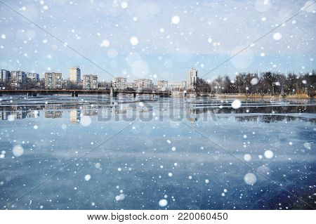 a frozen river or a pond on the background of the city landscape. Ice, ice rink, winter, pond