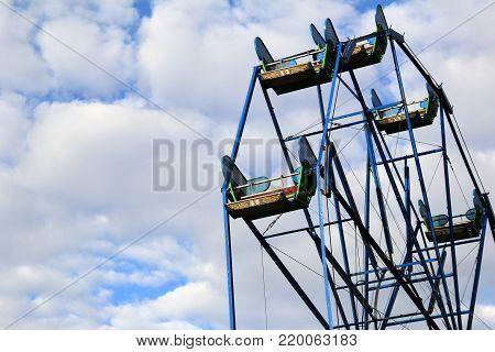 Image of carnival ride, everyone's favorite Ferris wheel, set against deep blue skies with puffy clouds background.