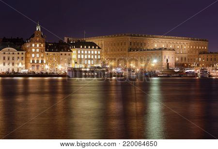 STOCKHOLM, SWEDEN - DEC 27, 2017: Nightscape of the Royal castle in central Stockholm in warm yellow light reflecting in the sea. Sweden, December 27, 2017
