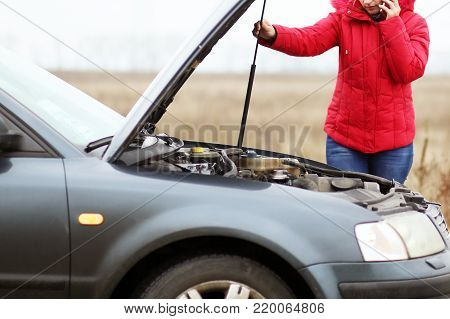 Breakdown of the car on the road. The girl opened the hood of her car