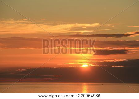 Horizontal image of ocean sunrise, with shades of cream and  orange, with sun peeking through the clouds over the horizon.