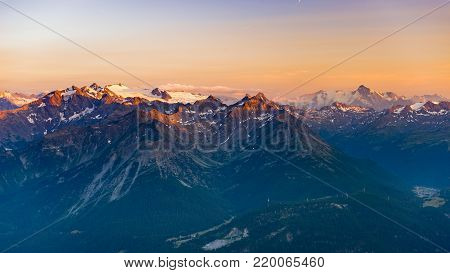 Last soft sunlight over rocky mountain peaks, ridges and valleys of the Alps at sunrise. Extreme terrain landscape at high altitude in Valle d'Aosta, scenic travel destination in Italy.