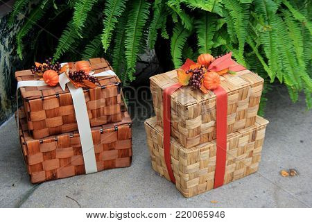 Pretty picnic baskets wrapped in colorful holiday ribbons, set on sidewalk next to large fern plant.