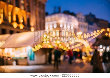 Abstract Blurred Bokeh Boke Background Of Traditional Christmas Market In Night European Town. Evening Street Decorated With Festive Christmas Xmas New Year Illuminations.