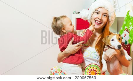 Happy woman wearing Santa hat with baby girl daughter and smiling Jack Russel Terrier dog