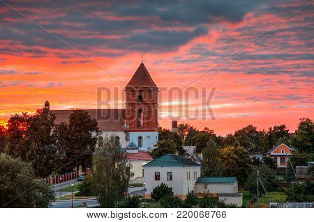 Mir, Belarus. Amazing Sunset Over Landscape Of Village Houses And Saint Nicolas Roman Catholic Church In Mir, Belarus. Famous Landmark. Historical Architectural And Cultural Heritage