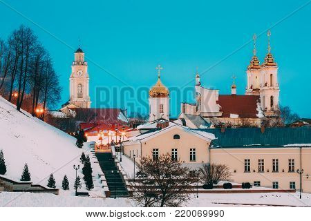 Vitebsk, Belarus. Winter Evening View Of Famous Landmarks Is Old Town Hall, Monastery Of The Holy Spirit And Church Of The Resurrection Of Christ In Night Street Lights Illumination. Blue Hour Time