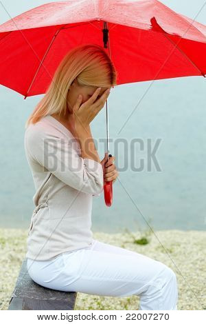 Portrait of sad young girl sitting on bench with umbrella