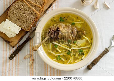 Chicken soup zama traditional Moldovan or Romanian soup served with cheese, bread and garlic. Rustic style, selective focus.