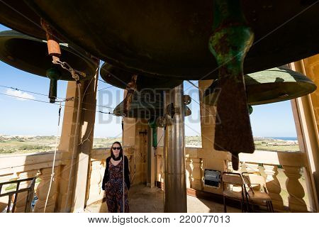 Tourist on clock tower on Church of Saint John The Baptis on Gozo island. Sacral architecture of Malta.