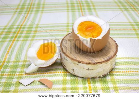 Boiled fresh egg for the breakfast on the wooden birch stand for eggs. Broken beige hen egg and pieces of shells, bright orange yolk