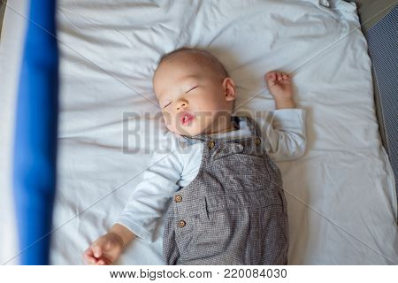 Cute little Asian 1 year old toddler baby boy child sleeping in baby cot, Peaceful kid lying on baby bed while sleeping with windows light at his face, Daytime sleep concept (shallow depth of field)