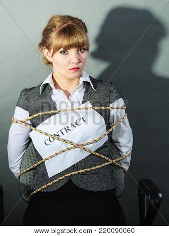 Upset businesswoman bound by contract terms and conditions.  Helpless woman tied to chair become slave. Business and law concept.