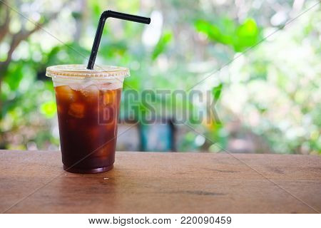 Plastic cup of iced black coffee with blur nature background