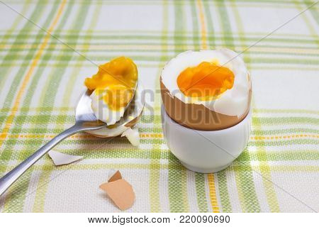 Boiled fresh smash broken egg for the breakfast on the porcelain stand for eggs. Broken beige hen egg and pieces of shells, bright liquid orange yolk in the spoon