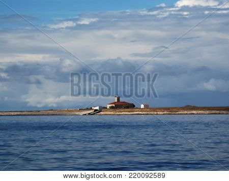 An old lighthouse on the empty,desert island at cloudy day