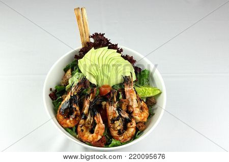 Sálad with fresh avocado and grilled prawn with light grey backdround