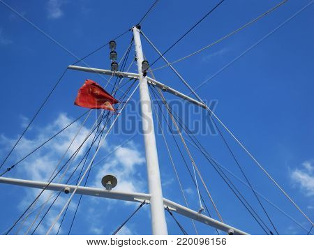 A dirthy,red kitchen apron on top of mast at sunny day under the blue sky