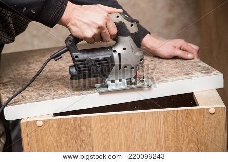 Master cuts wood with a jig saw .