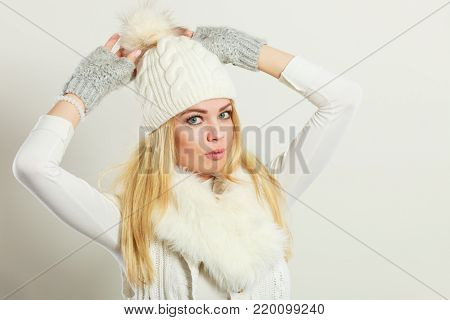Winter fashion. Young blonde woman wearing fashionable wintertime clothes white fur scarf, woolen cap and gloves, studio shot