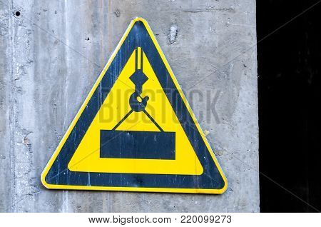 Sign on the wall. Cautiously, the load may fall. Building sign.