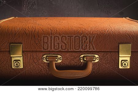 Old vintage, retro leather suitcase on dark background. Front view, horizontal, copy space, toned
