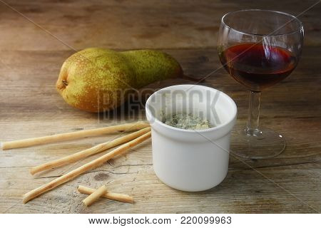 potted blue stilton cheese in a ceramic jar, port wine, pear and some nibble sticks on a rustic wooden table, copy space, selected soft focus, narrow depth of field