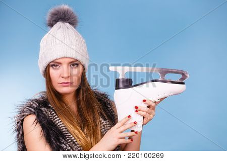 Winter, sport, people concept. Beautiful girl with white skate. Young lady has cap and fur vest.