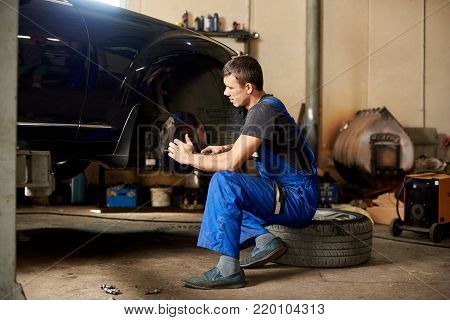 An auto mechanic in a dirty work uniform repairs front wheel of car in the garage. The guy looks carefully at the problem