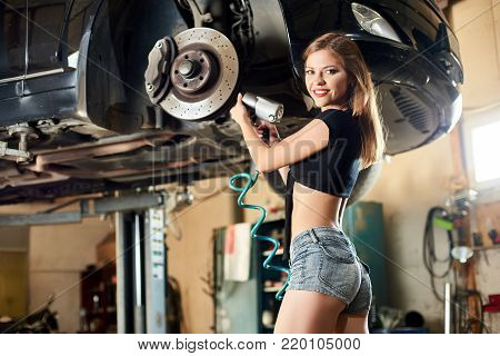 Beautiful Girl In Blue Denim Shorts Is Tightening The Bolts Of A Black Car
