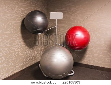 Three diferent sized exercise balance balls on a rack in the cornor of a hotel gym.