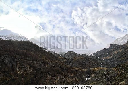 Looking up at the rugged Swiss Alps with clouds.